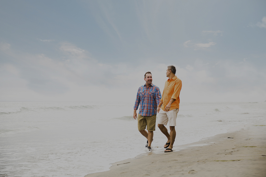 Affectionate interracial gay couple at a beach.